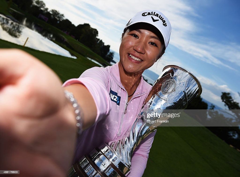 Lydia Ko of New Zealand imitates a 'selfie' as she poses with the trophy during a ceremony following after winning the Evian Championship Golf on September 13, 2015 in Evian-les-Bains, France.