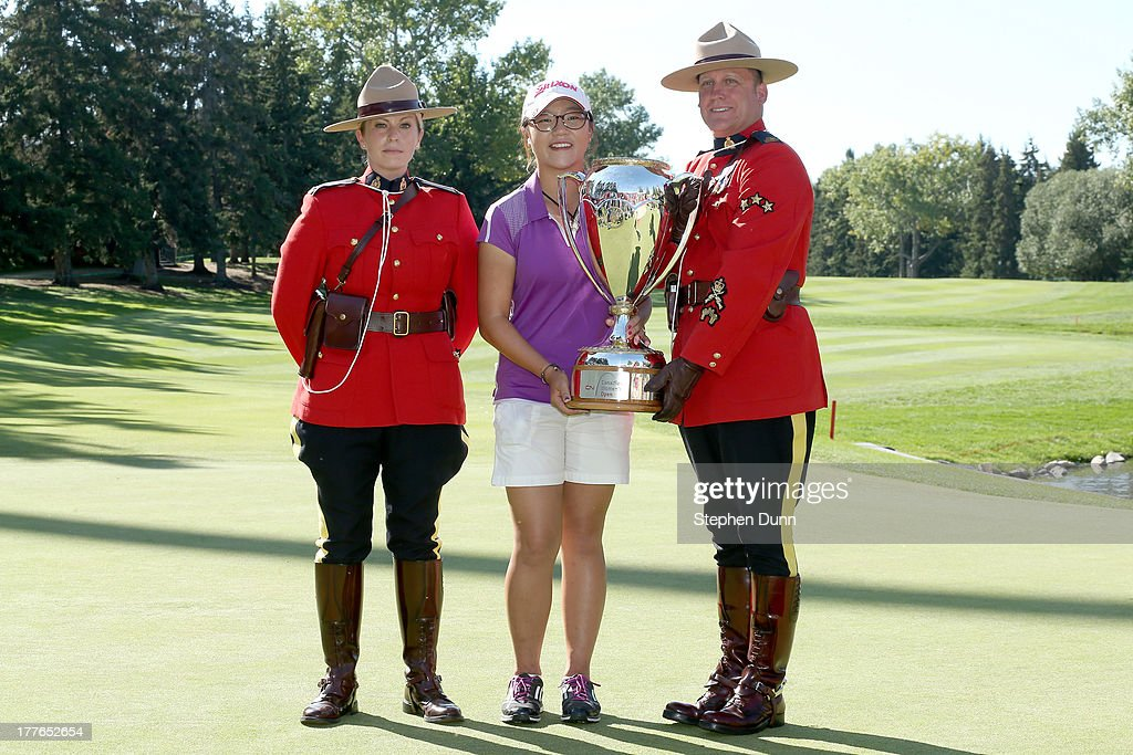 Lydia Ko of New Zealand poses with her trophy and two members of the Royal Canadian Mounted Police following her five stroke victory during the final round of the CN Canadian Women's Open at Royal Mayfair Golf Club on August 25, 2013 in Edmonton, Alberta, Canada.