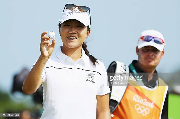 Lydia Ko of New Zealand poses with the golf ball she used to make a holeinone on the eighth hole during the third round of the Women's Individual...