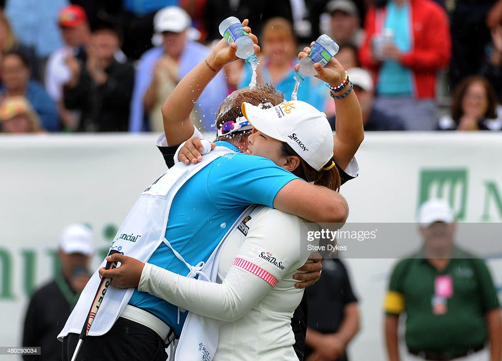 Lydia Ko of New Zealand pours water on Inbee Park of South Korea and her caddie after Park won the Manulife Financial LPGA Classic at the Grey Silo Golf Course on June 8, 2014 in Waterloo, Ontario, Canada.