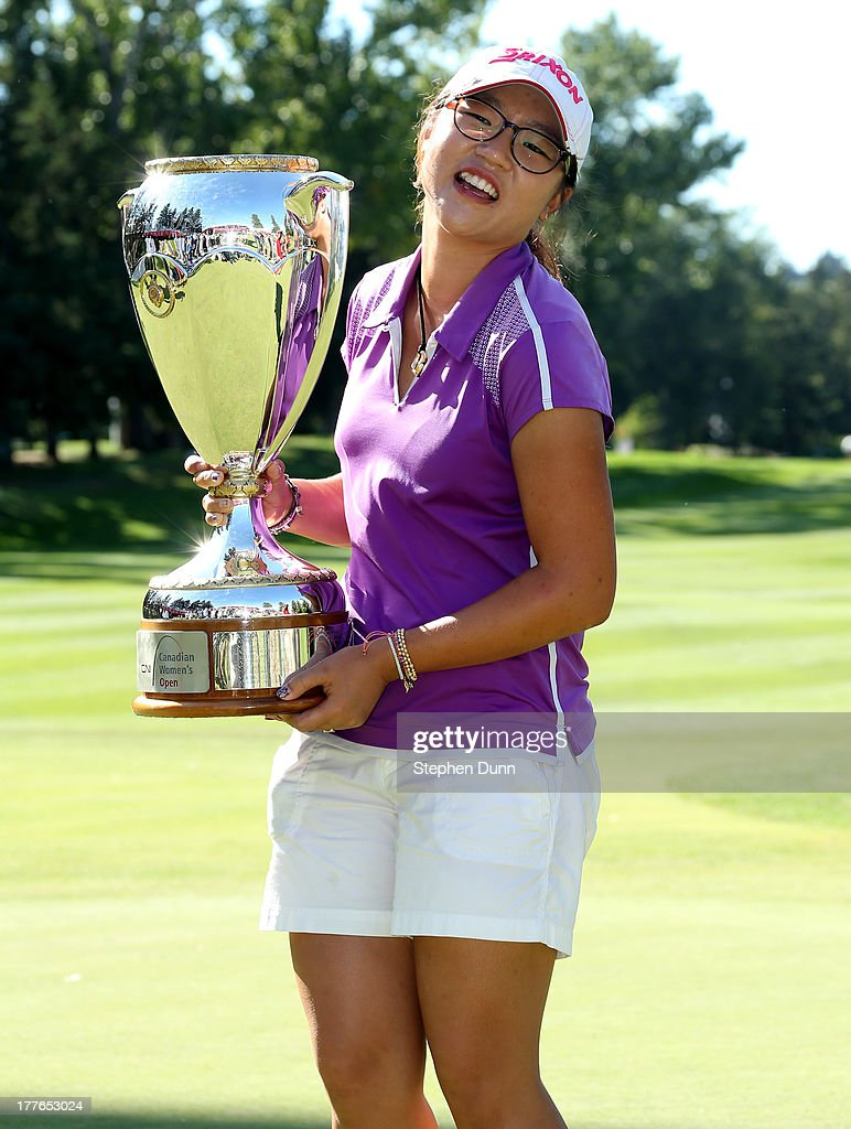 Lydia Ko of New Zealand reacts to the weight of her trophy after holding it up for a few minutes while posing with it following her five stroke victory during the final round of the CN Canadian Women's Open at Royal Mayfair Golf Club on August 25, 2013 in Edmonton, Alberta, Canada.