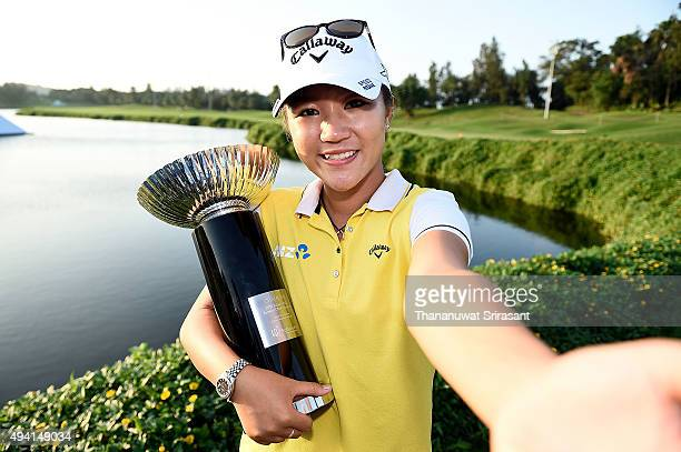 Lydia Ko pretends to take a selfie while holding the trophy on the 18th green after winning 2015 Fubon LPGA Taiwan Championship on October 25 2015 in...