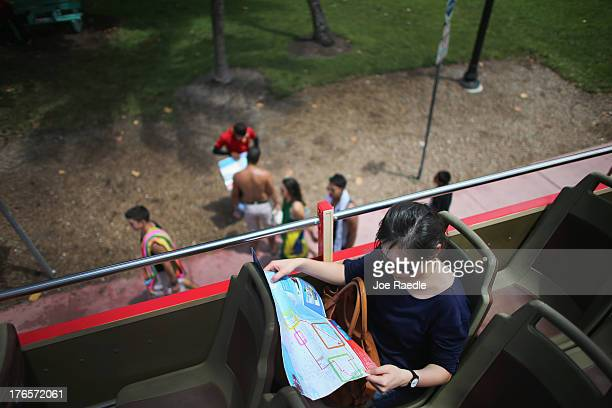 Lydia Teo on vacation from Singapore reads a tourists map as he and other tourists enjoy the view from the Big Bus Tour double decker bus during a...