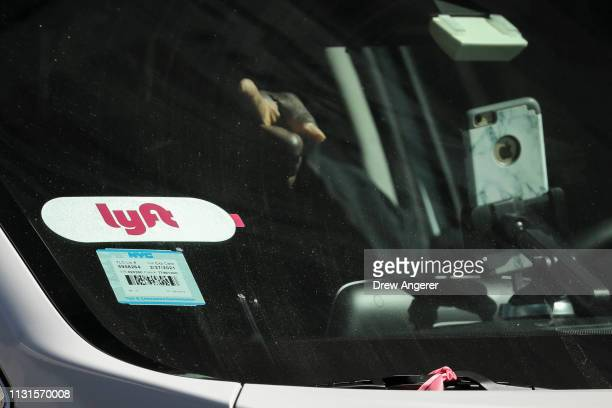 Lyft logo is displayed on a vehicle driving through Times Square March 19 2019 in New York City Lyft the popular ridehailing service and competitor...