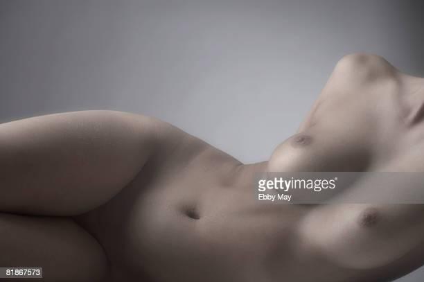 lying nude - nackte frau brüste stock-fotos und bilder