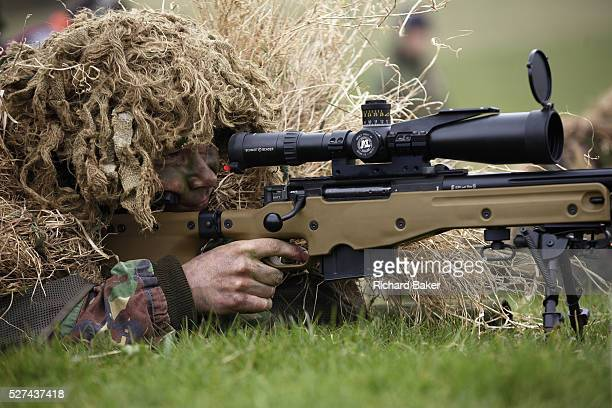 Lying on his stomach, a camouflaged British infantry soldier is seen looking down the telescopic sight of the new British-made Long Range L115A3...