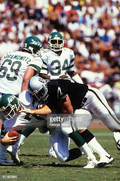 Lyle Alzado of the Los Angeles Raiders tackles quarterback Ken O'brien of the New York Jets during the game at the Los Angeles Memorial Coliseum on...
