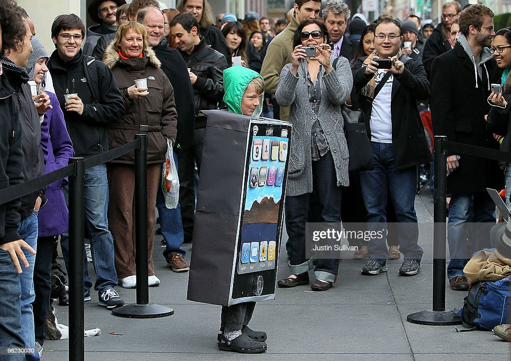 Lyle Haney (C) stops to have his picture taken as he wears a iPad costume while waiting in line to purchase the new iPad at an Apple store April 3, 2010 in San Francisco, California. Hundreds of people lined up hours before the Apple store opened to purchase the new iPad which debuted today.