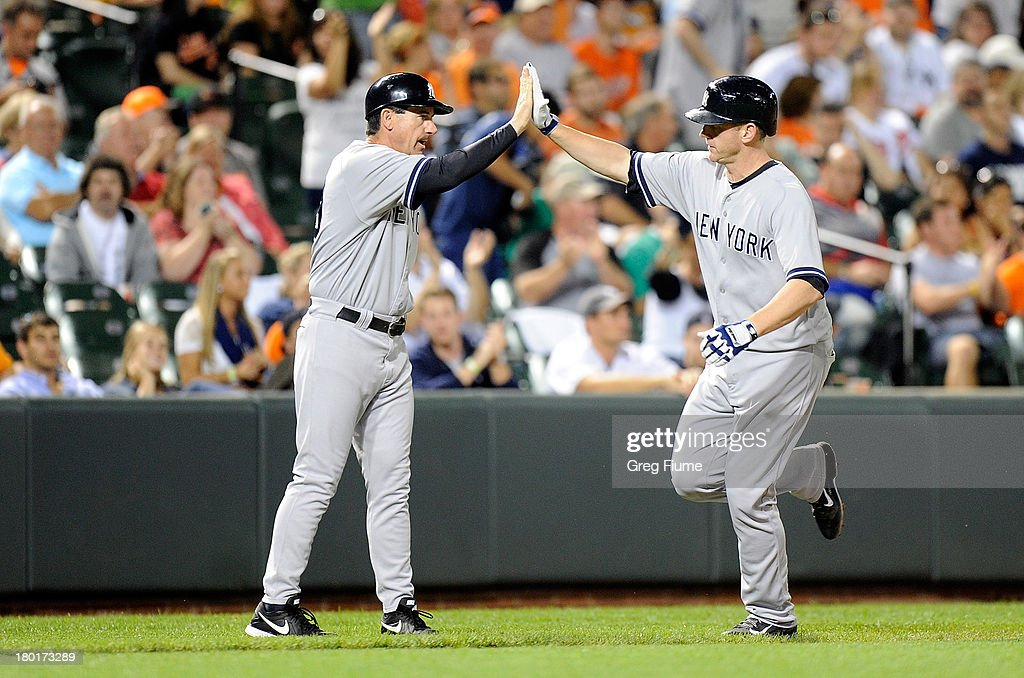 Lyle Overbay #55 of the New York Yankees celebrates with third base coach Rob Thomson #59 after hitting a home run in the eighth inning against the Baltimore Orioles at Oriole Park at Camden Yards on September 9, 2013 in Baltimore, Maryland.