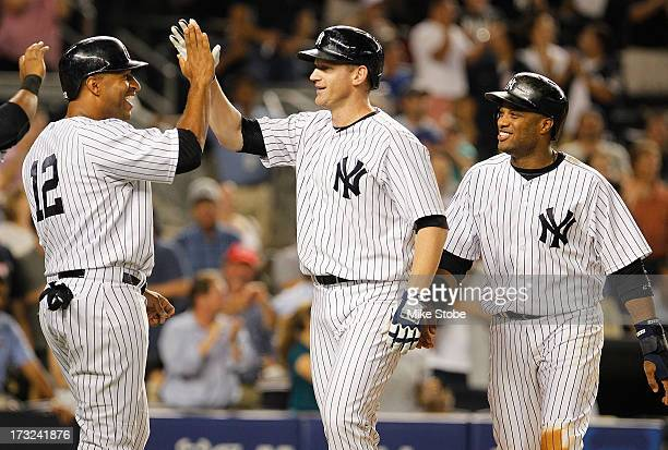 Lyle Overbay of the New York Yankees is greeted by Robinson Cano and Vernon Wells after hitting a grandslam in the sixth inning against the Kansas...