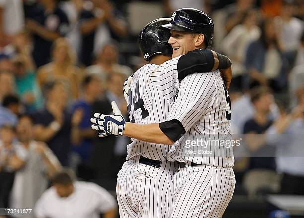 Lyle Overbay of the New York Yankees is hugged by Robinson Cano after hitting a grandslam in the sixth inning against the Kansas City Royals at...