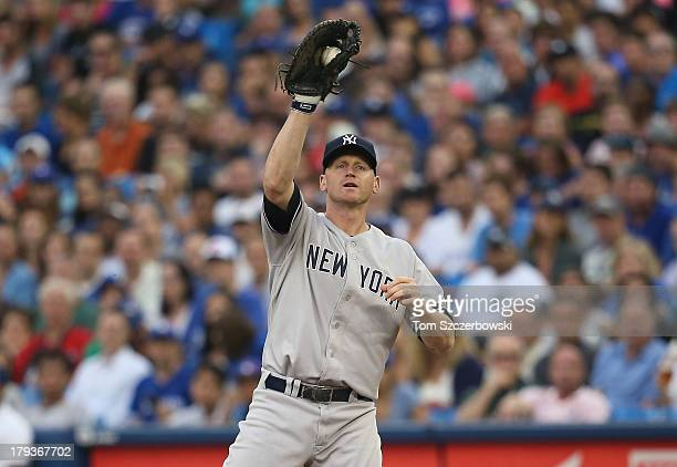 Lyle Overbay of the New York Yankees records the putout at first base to end the first inning during MLB game action against the Toronto Blue Jays on...