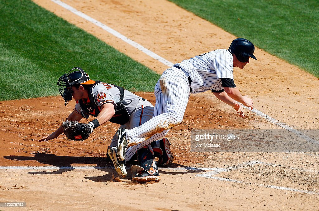 Lyle Overbay #55 of the New York Yankees scores in the sixth inning as Taylor Teagarden #31 of the Baltimore Orioles can't come up with the ball at Yankee Stadium on July 6, 2013 in the Bronx borough of New York City.