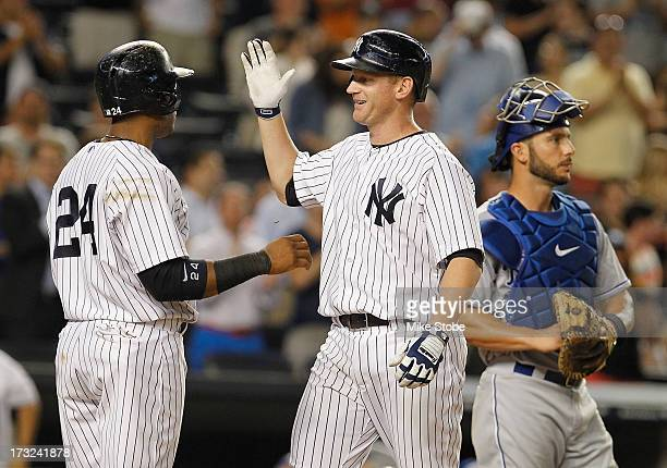 Lyle Overbay of the New York Yankeesis greeted by Robinson Cano after hitting a grandslam in the sixth inning against the Kansas City Royals at...