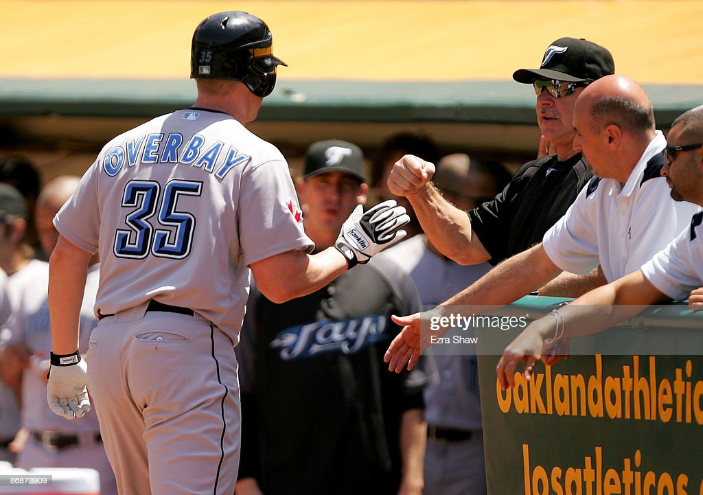 Lyle Overbay #35 of the Toronto Blue Jays is congratulated by his teammates after hitting a solo home run in the second inning of their game against the Oakland Athletics on May 9, 2009 at the Oakland Coliseum in Oakland, California.
