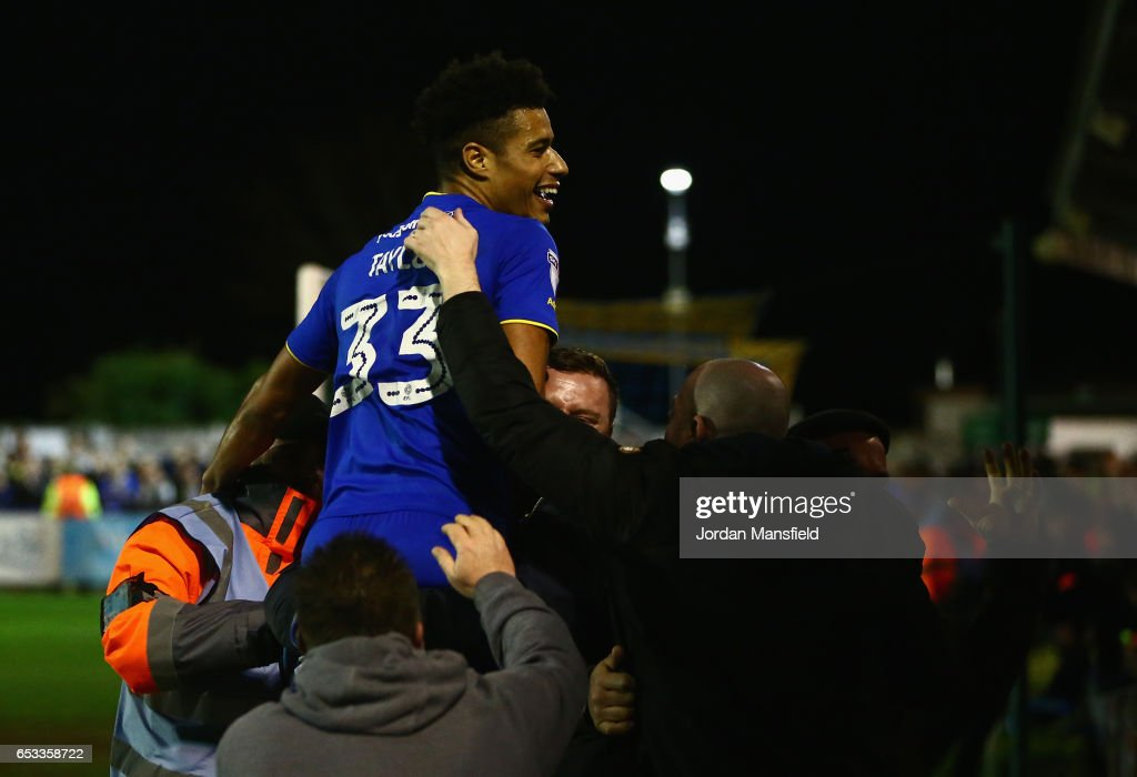 Lyle Taylor of A.F.C. Wimbledon celebrates with fans after team-mate Jake Reeves scores during the Sky Bet League One match between A.F.C. Wimbledon and Milton Keynes Dons at The Cherry Red Records Stadium on March 14, 2017 in Kingston upon Thames, England.