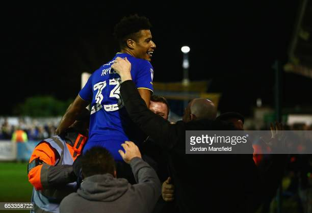 Lyle Taylor of AFC Wimbledon celebrates with fans after teammate Jake Reeves scores during the Sky Bet League One match between AFC Wimbledon and...