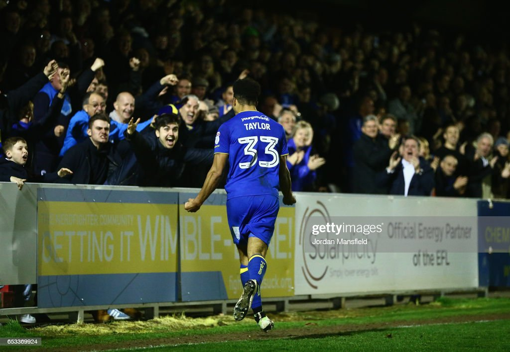 Lyle Taylor of A.F.C. Wimbledon celebrates with the fans after scoring the second goal during the Sky Bet League One match between A.F.C. Wimbledon and Milton Keynes Dons at The Cherry Red Records Stadium on March 14, 2017 in Kingston upon Thames, England.