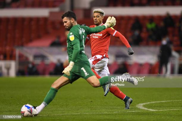 Lyle Taylor of Nottingham Forest runs in to tackle Ben Foster of Watford during the Sky Bet Championship match between Nottingham Forest and Watford...