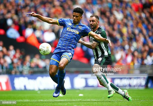 Lyle Taylor of Wimbledon tackles with Carl McHugh of Plymouth during the Sky Bet League Two Play Off Final match between Plymouth Argyle and AFC...