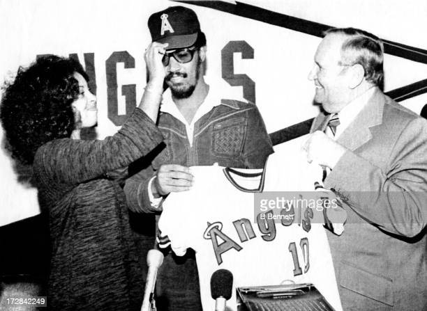Lyman Bostock with the help of his wife Yuovene tries on a California Angels hat after signing a fiveyear contract as owner Gene Autry helps him hold...