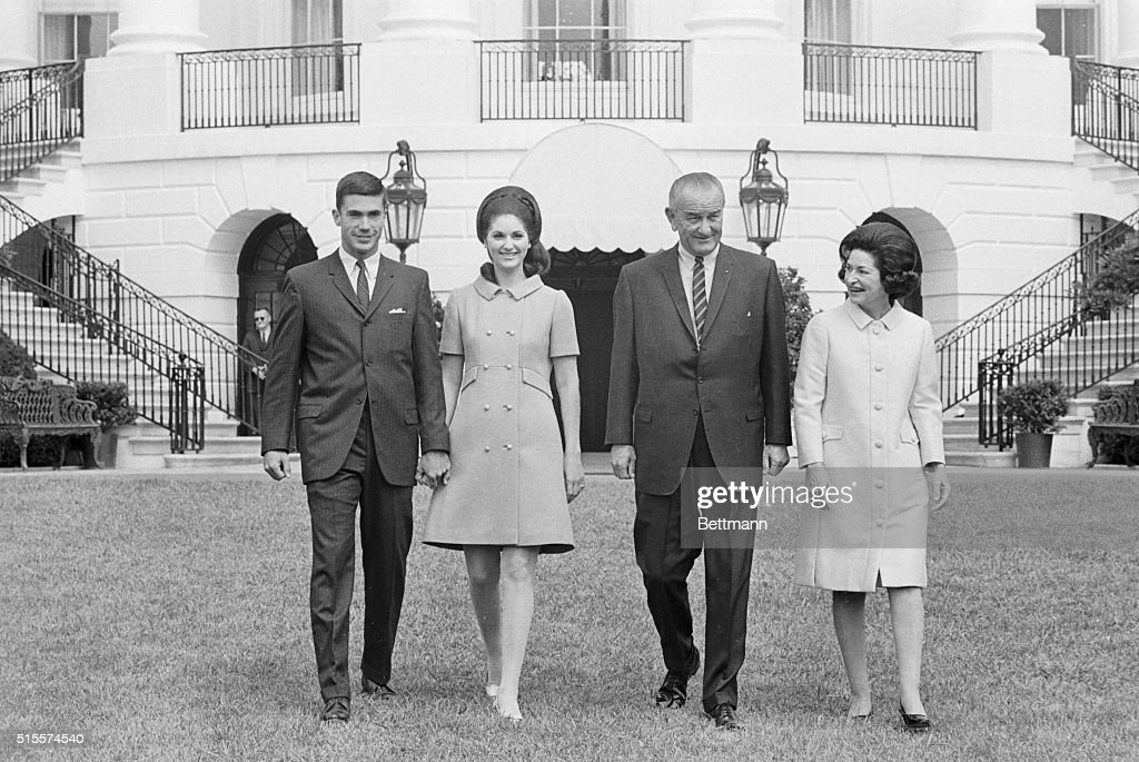 Lynda Bird Johnson, and her fiance, Marine Capt. Charles Robb, are joined by Pres. and Mrs. Johnson, during a picture-taking session on the White House lawn today. The couple will be married in a military ceremony at the White House early in December.