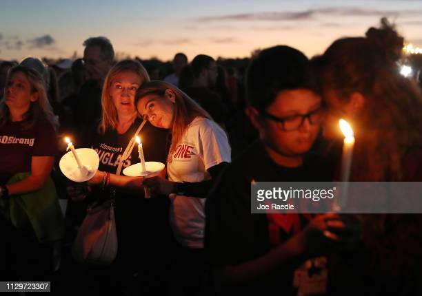Lynda Miller and Soona Buchanan hold their candles during a memorial service at Pine Trails Park for the victims of the mass shooting at Marjory...
