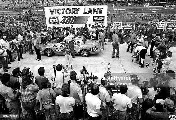 Lynda Petty wife of Richard Petty driver of the STP Pontiac holds up a preprinted poster declaring Richard Petty's 200 NASCAR win in Victory Lane at...