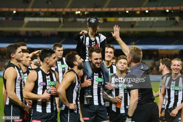 Lynden Dunn of the Magpies celebrates his first win with the club with his son during the round six AFL match between the Geelong Cats and the...