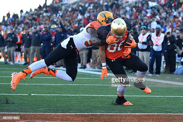Lynden Trail of the South team grabs the face mask of Ben Koyack of the North team during the first quarter of the Reese's Senior Bowl at Ladd...