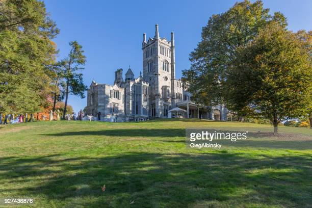 lyndhurst manor with halloween display, blue sky and trees in autumn colors (foliage) in tarrytown, hudson valley, new york. - tarrytown stock photos and pictures
