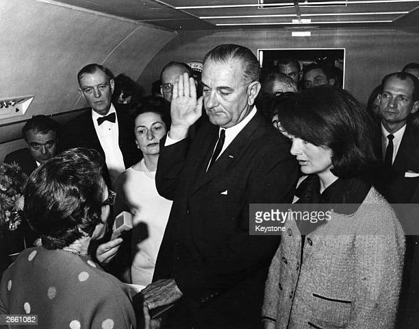 Lyndon Baines Johnson is sworn in as the 36th President of the United States of America on board the presdential aeroplane after the assassination of...