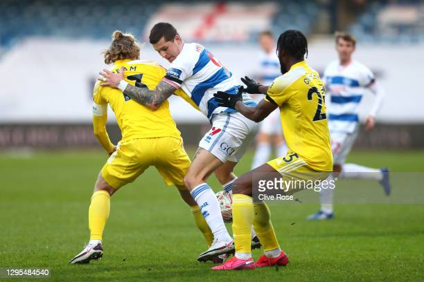 Lyndon Dykes of Queens Park Rangers is challenged by Tim Ream of Fulham and Josh Onomah of Fulham during the FA Cup Third Round match between Queens...