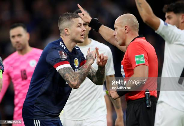 Lyndon Dykes of Scotland talks to Referee Szymon Marciniak after he disallows their second goal before later allowing it after VAR review during the...