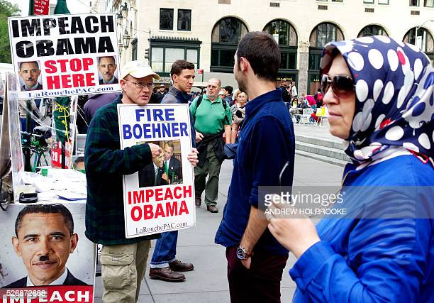 Lyndon LaRouche supporters with signs calling for impeaching President Obama and firing Speaker of the House John Boehner Signs with Hitler mustache...
