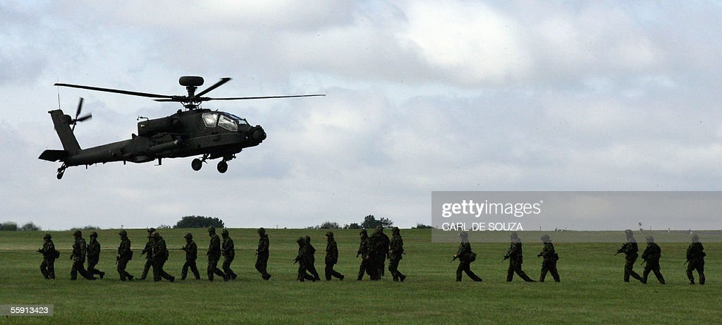 An Apache helicopter flies past soldiers : News Photo