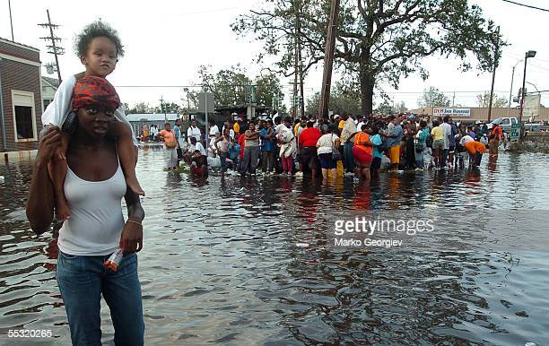 Lynell Wright carries Luric Johnson through a flooded intersection crowded with survivors awaiting rescue at the St Cloud bridge on August 30 a day...