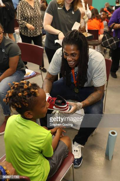 Lynetta Kizer of the Minnesota Lynx participates in a community event giving away shoes and socks at Payne Elementary in Washington DC on Jun 6 2018...