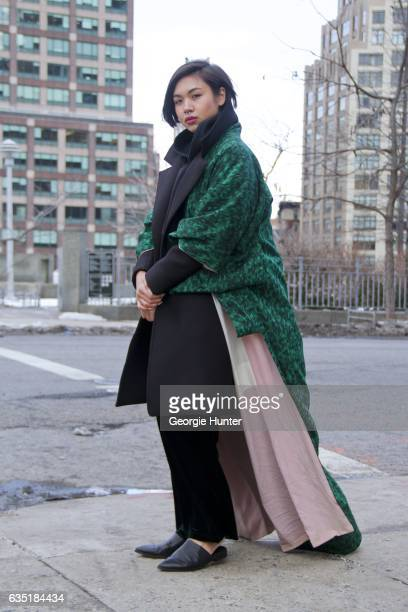 Lynn Kim Do is seen at Spring Studios outside the Phillip Lim show wearing green silk thifted kimono black neoprene three quarter length coat with...