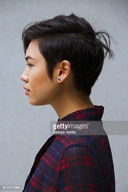 Lynn Kim Do wearing red and blue vintage sheer plaid tartan dress and gunmetal silver stud earrings with short cropped hair swept to the side on...