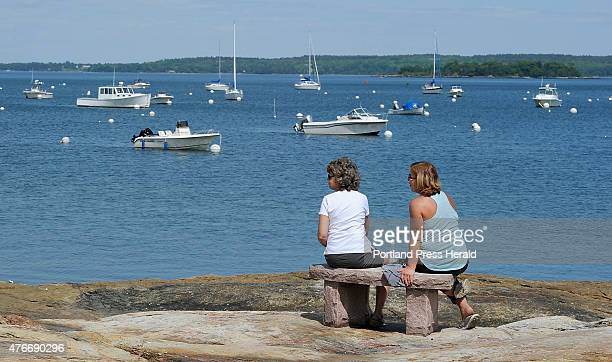 Lynn Lotfey left and her friend Wendy Morganstern both of Falmouth relax on a stone bench on the ledge at Falmouth Town Landing enjoying the view of...