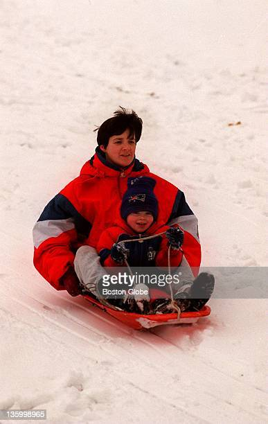 Lynn Stynes and her son Erik sled down hill as a way of enjoying this winter season's first snow fall. The storm dropped several inches in the Boston...