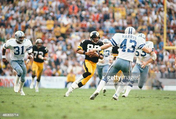 Lynn Swann of the Pittsburgh Steelers runs with the ball while pursued by Bob Breunig and Cliff Harris of the Dallas Cowboys during Super Bowl XIII...