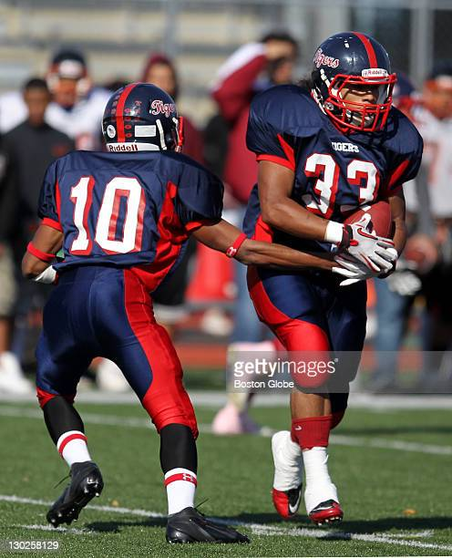 Lynn Tech Football QB Kennedy Gomes left hands off to Pedro Martinez during game action