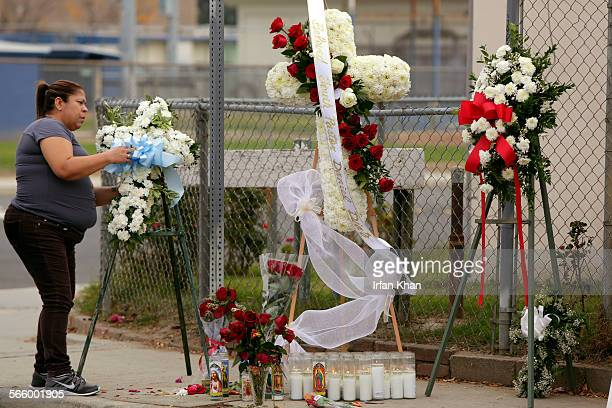 Lynna Moreno places a wreath at a make-shift memorial for a youth pastor Daniel Diaz who was shot and killed at the intersection of Park Avenue and...