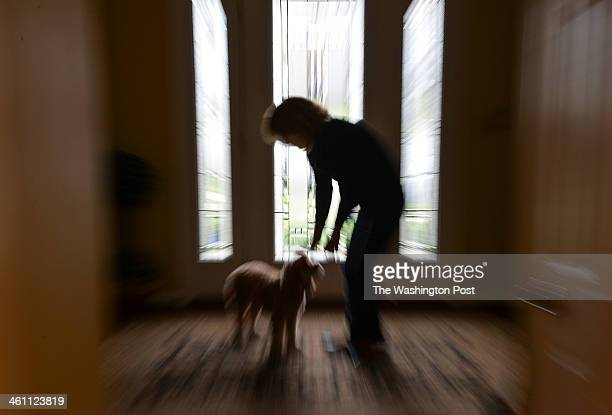 ASHBURN VA DECEMBER Lynne Beliveau is photographed at her home reaching for her cockapoo named Fenway on December 30 2013 in Ashburn Va Lynne...
