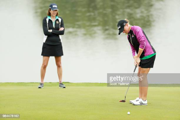 Lynne Doughtie Chairman and CEO of KPMG waits on a green alongside Stacy Lewis during the proam prior to the start of the KPMG Women's PGA...