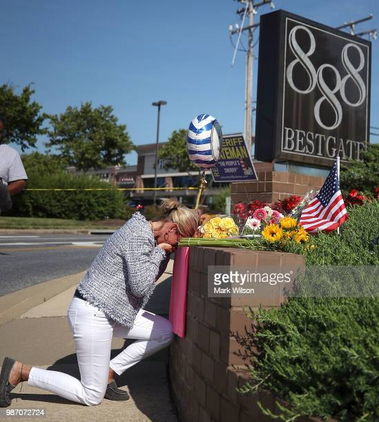 Lynne Griffin pays her respects at a makeshift memorial near the Capital Gazette where 5 people were shot and killed by a gunman on Thursday on June...
