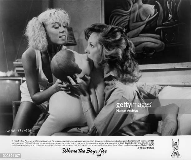 LynnHolly Johnson helps Wendy Schaal blow a doll in a scene for the TriStar movie Where the Boys Are '84 circa 1983