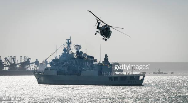 Lynx helicopter flies by Portuguese Navy frigate NRP Alvares Cabral laying at anchor in Tagus River during the commemoration of the 100th anniversary...